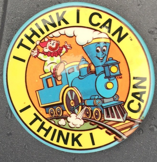 2.25 inches, round, metal back with pin and clasp promotional button for The Little Engine that Could. Illustration of Blue train with a smiling face and clown in tow. Brown Railroad tracks, Blue train with white smoke, trimmed in yellow, highlighted in orange with blue trim button edge and black lettering. Curl Text: 1986 by Platt & Munk The Putnam Grosset Group
