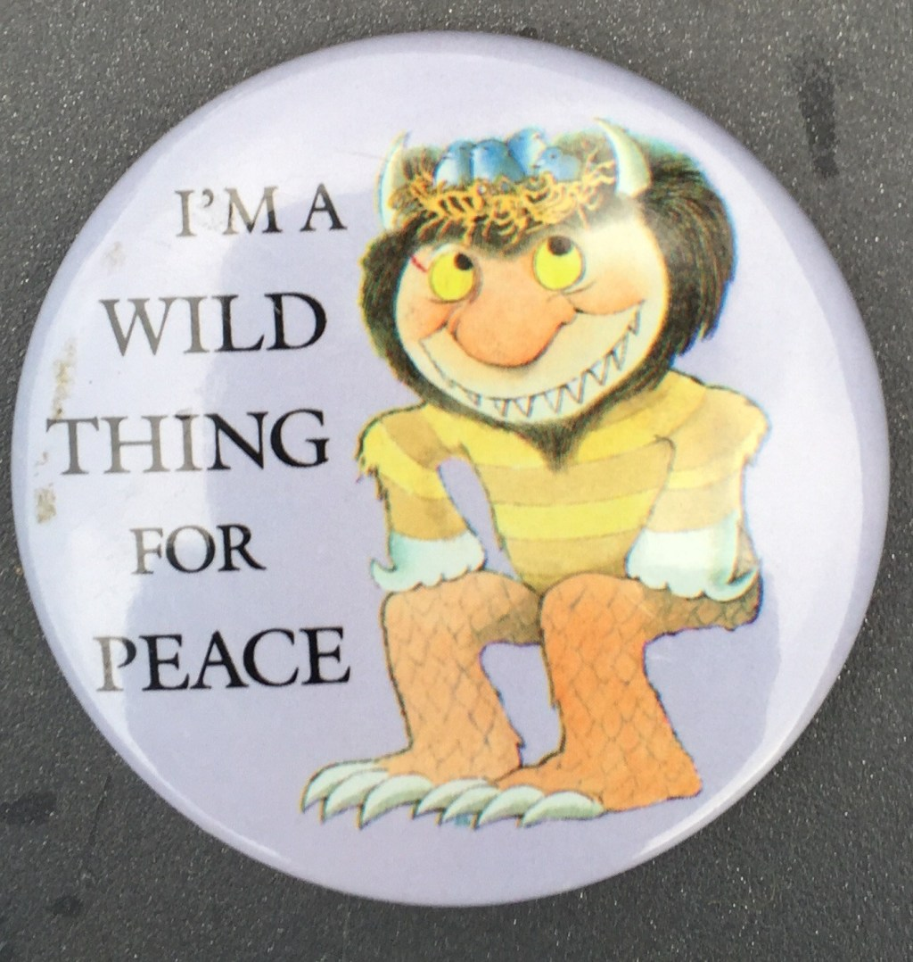 2.25 inches, round, metal w/pinback and clasp promotional button for Big Book for Peace. Featuring Maurice Sendak's Wild Thing illustration with lavender background, white toe-nails, orange fur legs, white claws yellow and tan horizontal striped shirt brown hair white fangs, yellow eyes with black pupils, white horn and blue crown w/ wheat colored straw, pink face, black text, Curl Text: The Big Book for Peace Dutton Art ©1990 Maurice Sendak