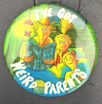 2.25 inches, round, metal w/pinback and clasp promotional button for Weird Parents. Illustration has white text green background highlighted with yellow. Parents sitting on bed father holding blue book sitting next to mother and child. Red lantern with yellow light. Blue shining through window. Curl Text: None