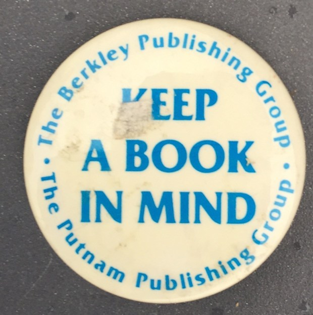 1.75 inches, round, metal pinback with clasp promotional button for The Berkley and Putnam Publishing Groups. Blue Lettering design on white back ground. Slogan encircled by publisher's name. Curl Text: None.
