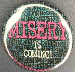 """1.5 inches, round metal pinback with clasp promotional button for the soon-to-be-released 1990 Hollywood film based on Stephen King's 1987 novel """"Misery"""". Design is on Black background layered with a repeating """"Misery"""" in green lettering and tagline in white text. Curl Text: © 1990 Castle Rock Entertainment All Rights Reserved"""
