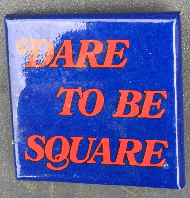 1.5 inches, square, cardboard pinback and clasp promotional button for the book Dare to Be Square. Blue background with red text. Curl text: None