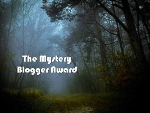 white lettering in the mid left corner spelling out The Mystery Blogger Award placed on a photo of a foggy forest with an open pathway