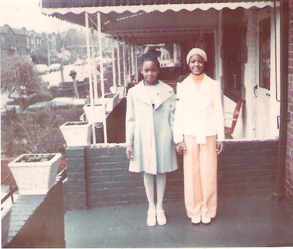 two young girls holding hands standing on a porch
