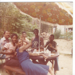 Photo of 4 men and 2 women sitting under an outdoor umbrella