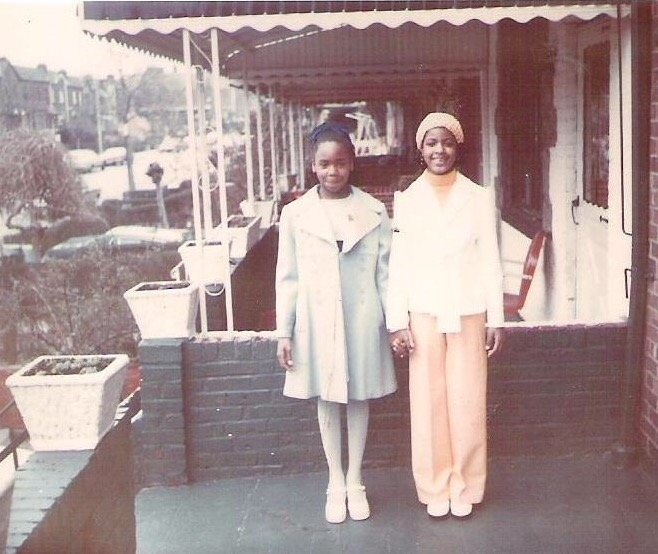 a photo of two young girls standing on a porch holding hands