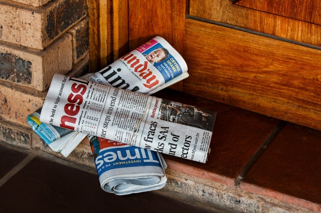 image of newspapers piled at the door