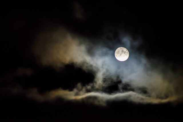 night sky with clouds around a full moon